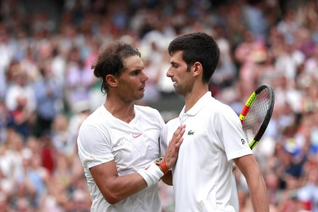 Novak Djokovic (right) shakes hands with Rafael Nadal after his win on day twelve of the Wimbledon Championships at the All England Lawn Tennis and Croquet Club, Wimbledon.