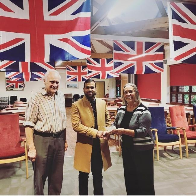 Mohammed Bahar Uddin hands a donation to Mr and Mrs Baldwin of Claygate Community Centre. Image: Esher Tandoori via facebook