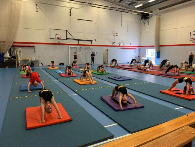 Gymnasts at the Spectrum Gymnastics Academy return to physically distanced training.