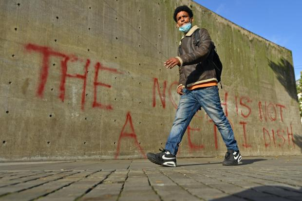 A man walks past graffiti reading 'the north is not a petri dish' in Manchester (Jacob King/PA)