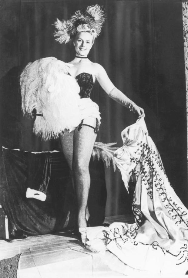 Striptease artist Phyllis Dixey (c.1914 - 1964), whose saucy revues at the Whitehall Theatre in London were legendary, poses fishnet stockings and suspenders, circa 1940. (Photo by Evening Standard/Hulton Archive/Getty Images)