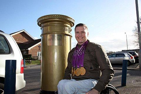 Golden glow: David Weir with post box commemorative plaque and four 2012 Paralympic gold medals