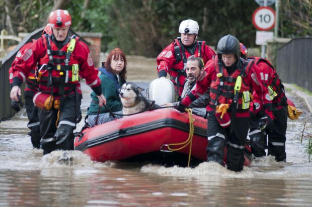 A couple and pets being rescued from their home in Thorncroft Drive, Leatherhead, on Christmas Eve