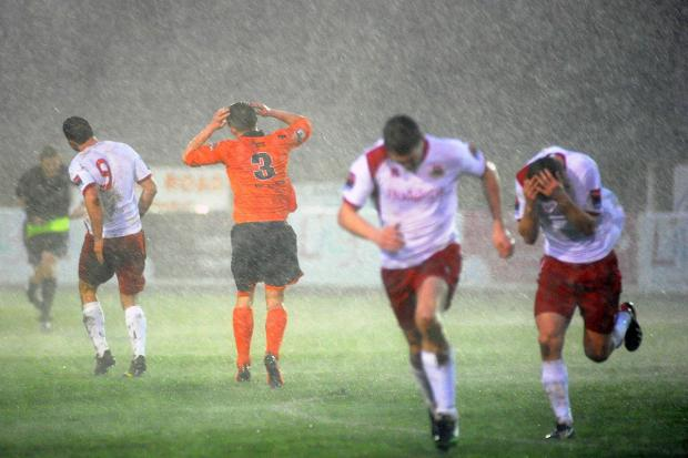 Surrey Comet: Run for it: Whitstable Town players run for cover during the storm that