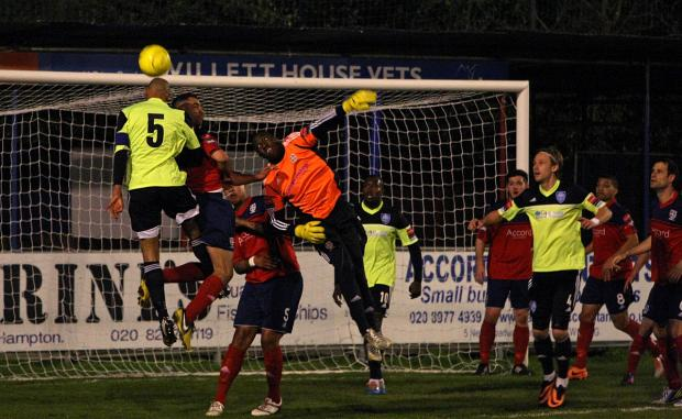 Up for it: Met Police skipper Steve Sutherland leaps above Hampton keep Rodney Chiweshe on Tuesday night