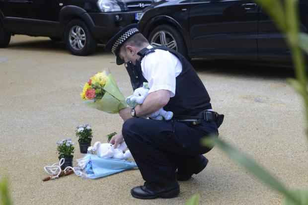 A police officer places flowers in the driveway of the family home