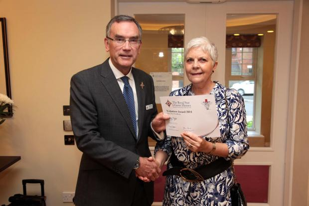 Mary Taylor receives a one-year volunteering certificate from the Star & Garter's chief executive Mike Barter