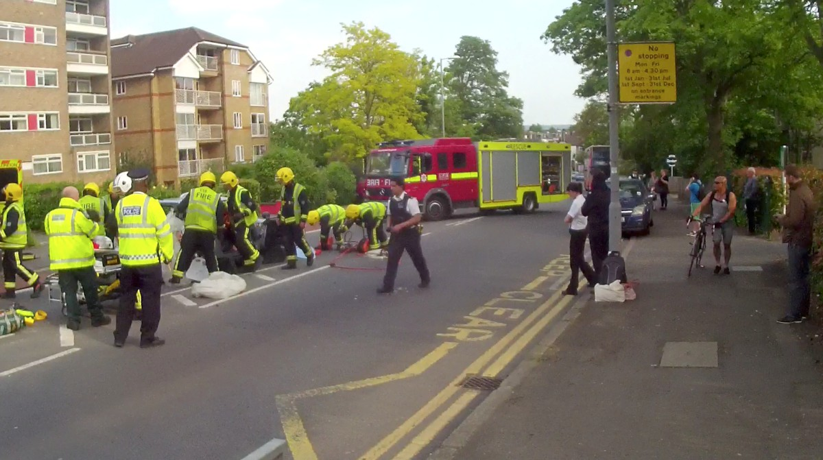 Emergency services rescue a driver after the crash yesterday afternoon in Ewell Road