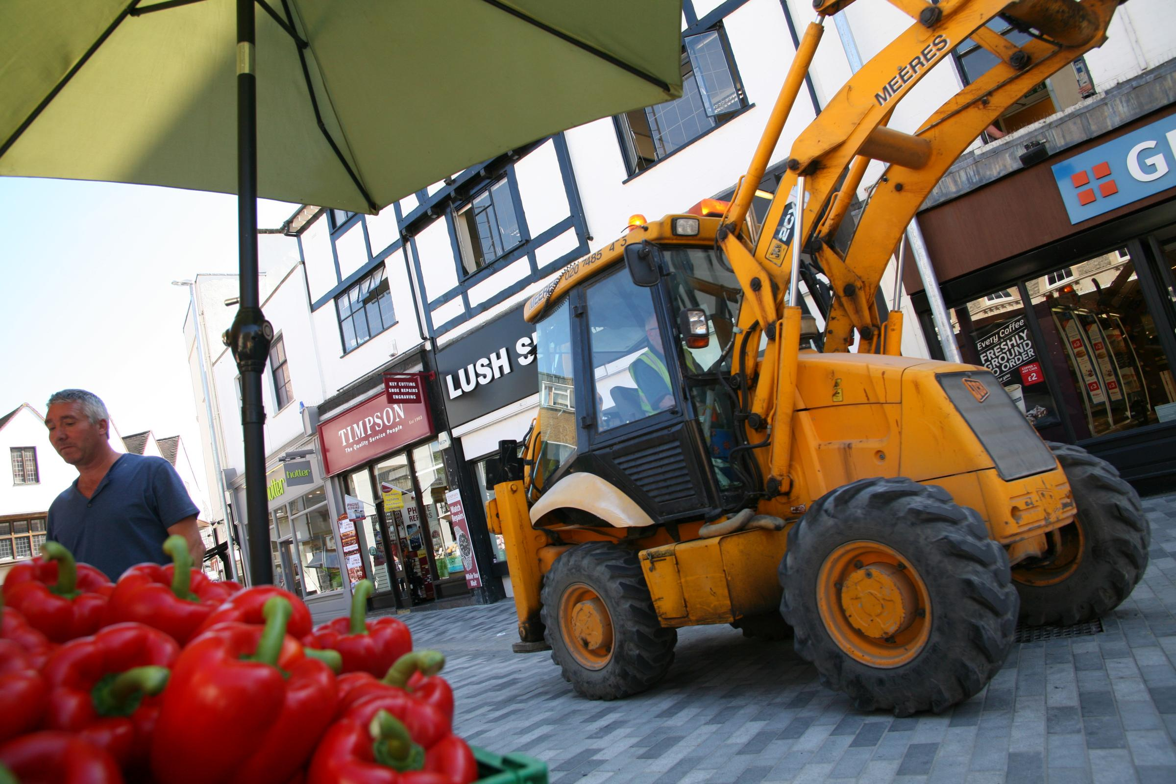A digger trundles past newly-opened fruit and veg stalls. Photo: Jon Sharman