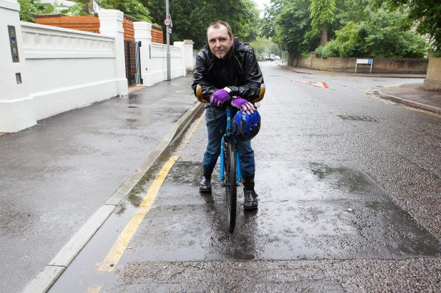 Cyclist John O'Connell in Langley Road, Surbiton, at the spot where he hit a pothole, since repaired
