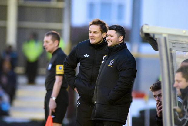 Team work: Neal Ardley and Simon Bassey share a joke on the touchline