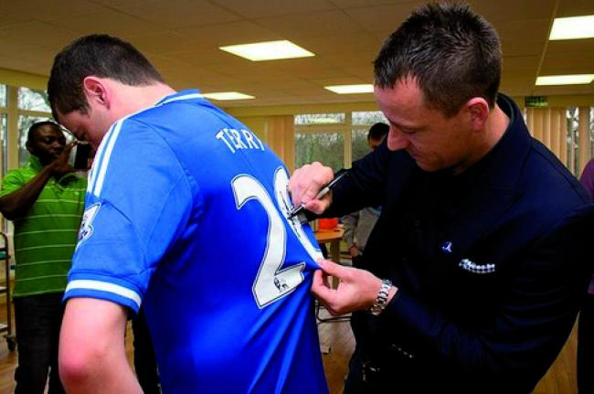 Chelsea through and through: John Terry signs a fan's shirt