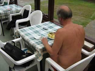A man eats his lunch in the buff