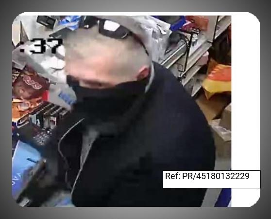 Police would like to speak to this man in connection with an armed robbery at a post office in Banstead.