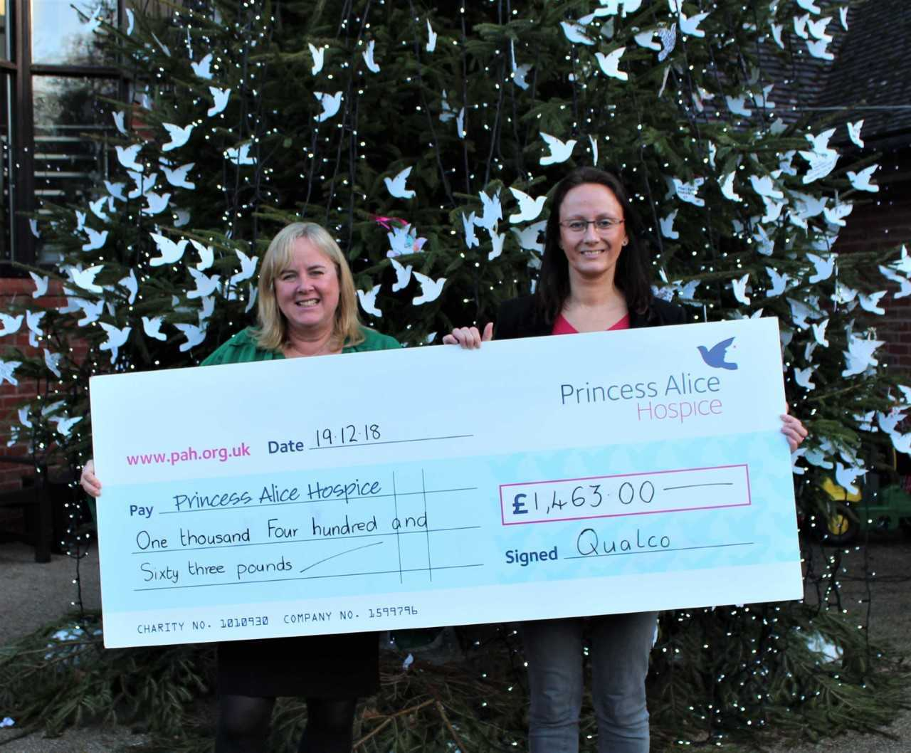 Jo de Buriatte, right, handing the giant cheque to Claire Woodward beside the Hospice Memory Tree covered in dove dedications