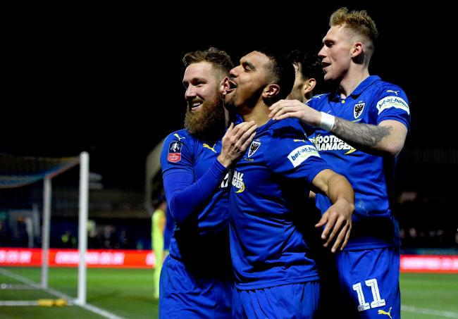 AFC Wimbledon's Scott Wagstaff celebrates scoring his side's third goal of the game with team-mate Kwesi Appiah (centre) during the FA Cup fourth round match at Kingsmeadow, London.