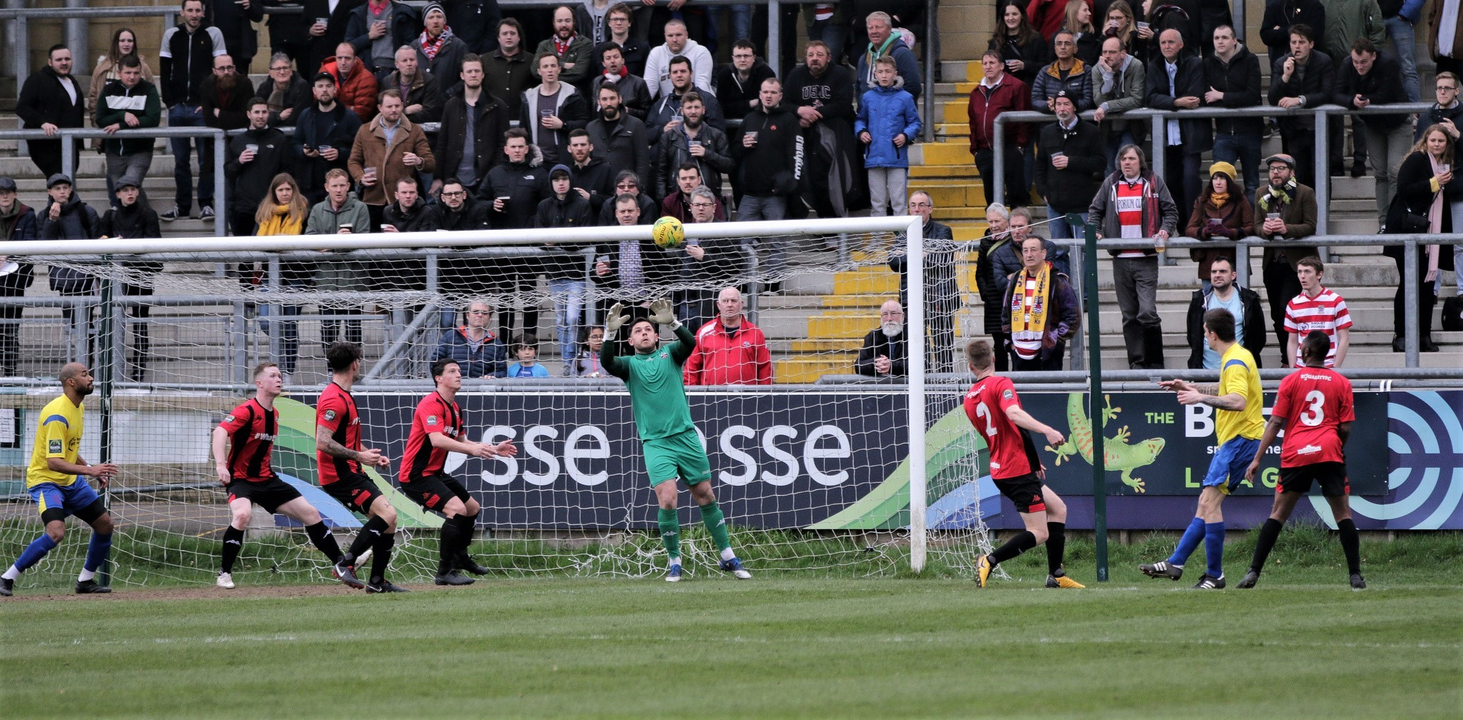 Dean Inman's header is saved at Lewes as Kingstonian's sizeable away support looks on. Pic: James Boyes.